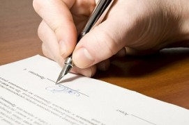 Close up of the hand holding the pen and signing the contract